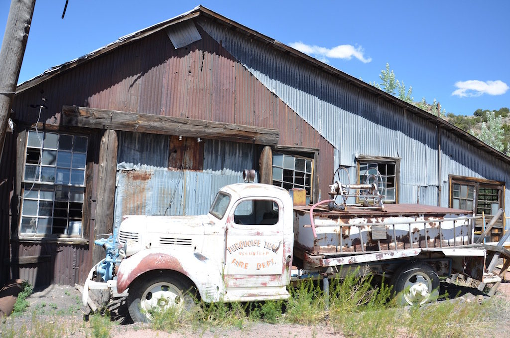 A few old rusting antique cars and trucks.